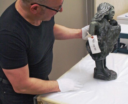 Winnipeg Art Gallery staff examines a sculpture before packing